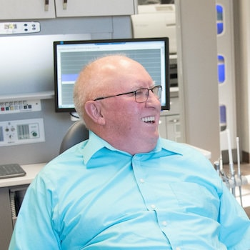 Man in a blue shirt smiling after his gum contouring as part of cosmetic dentistry in Bismarck ND
