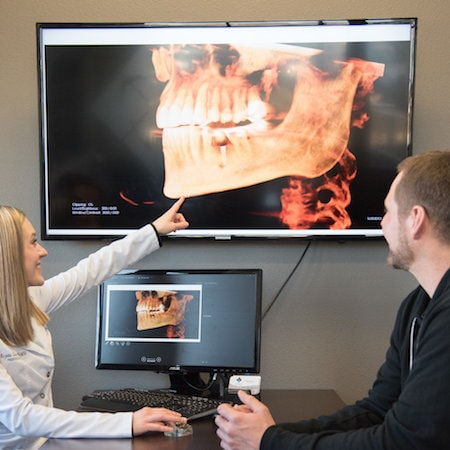 Dr. Sellers pointing at a large x-ray while a patient looks on. We use only the latest technologies to craft your dental implants in Bismarck, ND