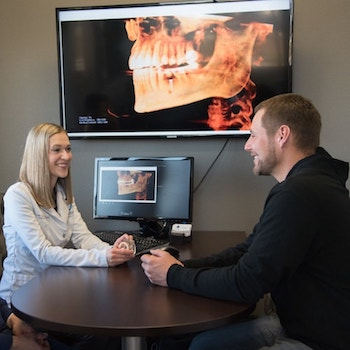 Top Bismarck prosthodontist, Dr. Sellers discussing dental implants with a patient