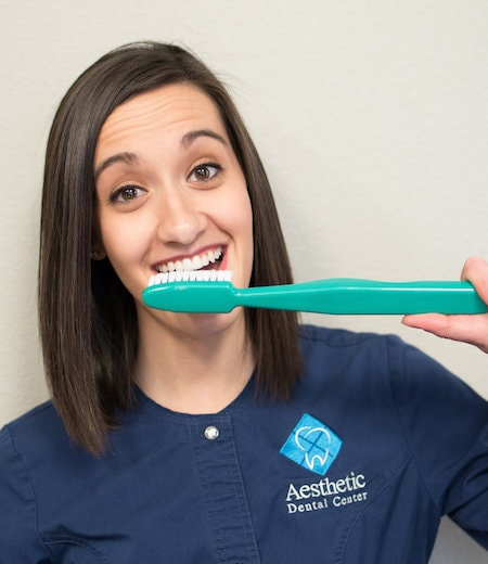 Shelby is a team member who is holding a huge toothbrush