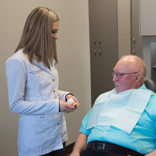 Dr. Sellers specializes in dental implant in Bismarck, ND. here she is shown explaining the procedure to a patient