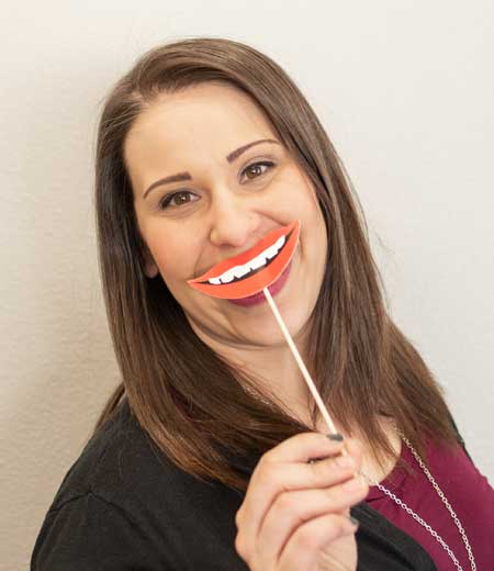 Courtney is on our team and has fun with our tooth props